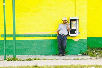 A farm worker uses a pay phone in Immokalee, Fla., after working in the tomato fields.