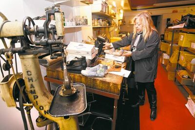 Photos by KEN GIGLIOTTI  / WINNIPEG FREE PRESS  Lisa Afanasiev stands next to an ancient stitching machine in her custom-shoe shop on Main Street.