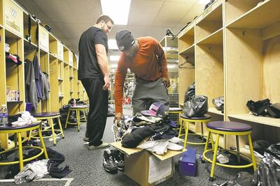 photos by mike deal / winnipeg free pressWinnipeg Blue Bombers� Cory Watson puts a pair of running shoes onto a pile of equipment being donated to a shelter as he cleans out his locker Sunday.