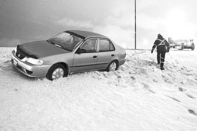 Tow truck operator pulls car out of ditch on Perimeter at Lagimodiere Boulevard on Monday.