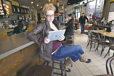 Jason Franson / THE CANADIAN PRESSTanis Miller watches a movie on her iPad at a coffee shop in Edmonton.
