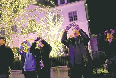Tourists photograph holiday displays in the Brooklyn borough of New York.