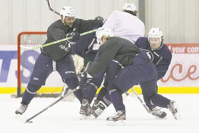 John Woods / THE CANADIAN PRESSJets defenceman Dustin Byfuglien (left) drives teammate Chris Thorburn (centre) into Ron  Hainsey (right) as Bryan Little (back) carries the puck during a Wednesday workout.