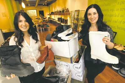 Sisters Pam Grynol (left) and Voula Sarlas at Soul Shoes and Accessories with some of the shoes collected for the United Way.