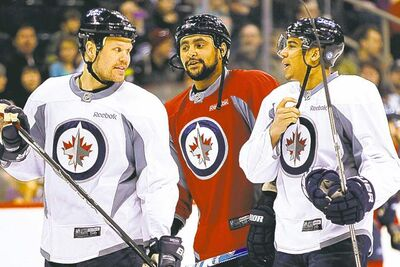 Kane chats with teammates Olli Jokinen (left) and Dustin Byfuglien during the public practice session.