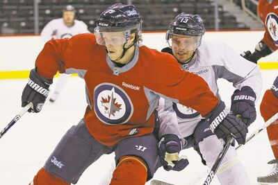 John Woods / the canadian pressDefenceman Tobias Enstrom (left) attempts to fend off the pesky pursuit of forward Kyle Wellwood on Day 3 of Winnipeg Jets training camp at the MTS Iceplex Tuesday.