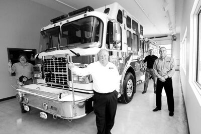 Five-alarm service: (left to right) Tony Berlis, owner Rick Suche, operations manager  Jim Peters and national sales manager Brian Nash with new truck for Valcartier, Que.Berlis   , owener Rick Suche , Jim Peters  Operations Mgr. Brian Nash National sales Mgr  with brand new  fire truck for  Valcartier Que