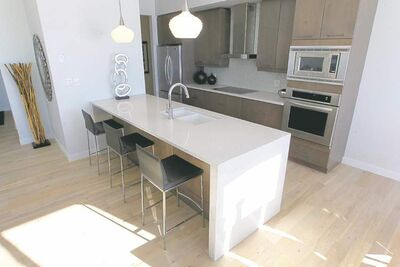 Beige quartz countertops and maple cabinets in the kitchen create a contemporary feel.