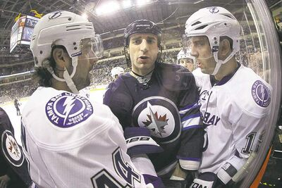 Tampa Bay's Nate Thompson (left) and Teddy Purcell have some friendly words for Winnipeg's Chris Thorburn during the second period Sunday.