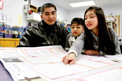 Juliana Valdoria with her father, Elmer, and brother, Jasch, at a parent-teacher conference. She loves to read, but 'needs to participate more in class.'