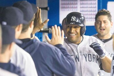 Ex-Blue Jay Vernon Wells celebrates in the Yankees' dugout after clubbing a seventh-inning homer against his former team on Friday night.