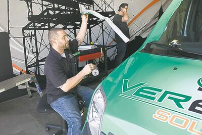 Shane Doser installs a vehicle wrap at Iconography Studios.