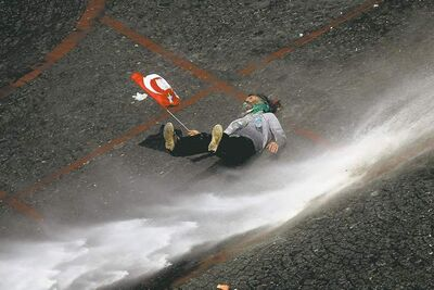 A protester holding a Turkish flag is thrown off his feat by a stream of water from a police water canon during clashes in Taksim square in Istanbul.