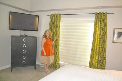 Carolyn Giese of Creative Window Coverings and Accessories shows blinds and side panels in a bedroom setting.