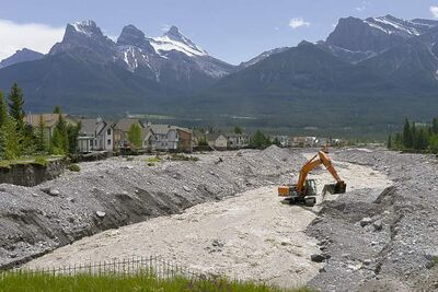 Excavators work on the Cougar Creek bed two days after it tore through Canmore, Alta., Saturday, June 22, 2013. THE CANADIAN PRESS/Jonathan Hayward