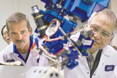 Canadian astronaut Chris Hadfield (left) and Gary Goodyear, minister of state for science and technology, inspect a robotic arm.