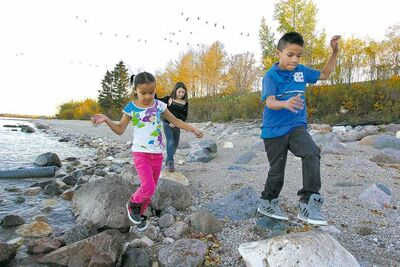 Little Saskatchewan First Nation evacuees Kenisty St Clair (from left), Anika Wetherill and Zach Cruly from play on the shore of Lake Winnipeg at Misty Lake Lodge last October.
