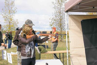 A prospective hunter gets some help aiming an air rifle at Provincial Hunting Day.