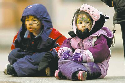 Logan Bancroft, 5, and his sister, Asia, 4, wait on Portage Avenue for the parade to start.