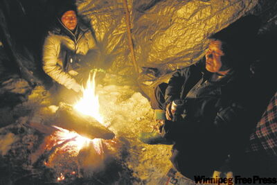 Mike enjoys the comforts of a warm fire and a cold beer in his riverbank shelter.