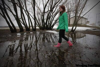 Amie Seier walks through some water on her family's property just outside St Norbert on Saturday.  The property floods once the floodway gates are raised.