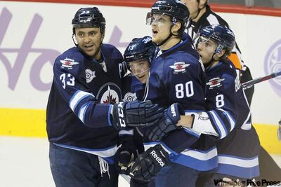 Winnipeg Jets Dustin Byfuglien (33), Kyle Wellwood (13), Nik Antropov (80) and Alexander Burmistrov (8) celebrate Wellwood's goal against the Carolina Hurricanes in first-period action at the MTS Centre today.