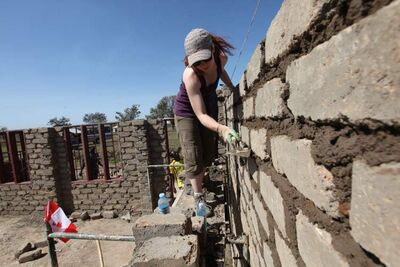 A member of the Canadian team scrapes away excess mortar on the wall.