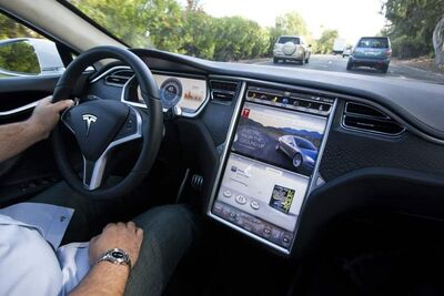 The 17-inch touch display of Tesla's Model S shows the music player and a website using its built-in web browser.