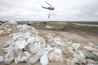 Members of the 2nd Battalion, PPCLI,  help load sandbags onto helicopter slings to be transported to weak sections of the dike running along the Assiniboine River, 25 kilometres from Portage la Prairie.