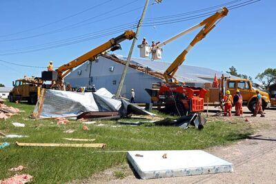 Manitoba Hydro crews work to restore power to Pipestone on Sunday after Saturday evening's powerful storm knocked down power lines throughout the community. The community centre (in the background) lost part of its roof during the storm and debris from a destroyed trailer also litters the ground.