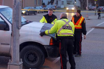 Police cover the front of a white pickup truck at the scene of a pedestrian collision Wednesday.
