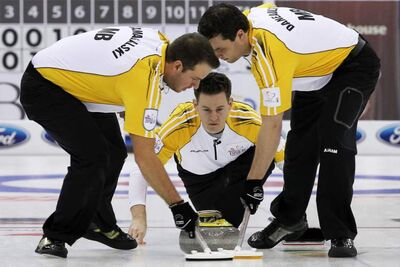 Manitoba skip Rob Fowler, centre, watches his shot as lead Derek Samagalski, left and second Richard Daneault sweep during a morning draw against Saskatchewan at the Tim Hortons Brier in Saskatoon, Sask. Thursday.