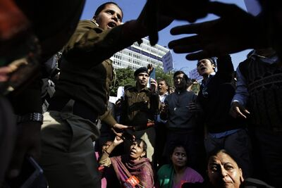 An Indian police officer tries to pacify protestors outside the Delhi Police headquarters during a protest in New Delhi, India, Wednesday, Dec. 19, 2012. The hours-long gang-rape and near fatal beating of a 23-year-old student on a bus in New Delhi triggered outrage and anger across the country Wednesday as Indians demanded action from authorities who have long ignored persistent violence and harassment against women. (AP Photo/Altaf Qadri)