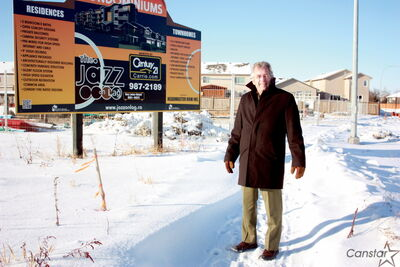 Century 21 real estate agent Georges Bohemier stands in front of a sign advertising the Jazz on Lag complex on Headmaster Row. The condos are expected to be completed in early 2014.
