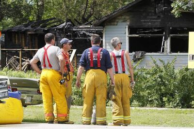 Winnipeg Beach firefighters look at the charred shell of a Prospect Street home in Winnipeg Beach. Two people died and one was sent to a Winnipeg hospital after a fire at the home early Sunday morning.