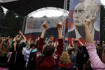 Daily morning exercises at the Seliger Forum 2011 summer camp, viewed by a heroic likeness of Putin.
