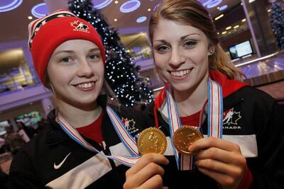 Ashleigh Brykaliuk (left) and Cassidy Carels show off their 2013 IIHF Ice Hockey U18 Women's World Championship medals after returning from Finland Sunday at James Richardson Winnipeg International Airport.