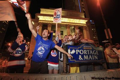 Hockey fans celebrate at Portage and Main in downtown Winnipeg after reading a report in The Globe and Mail newspaper that a NHL team maybe returning to Winnipeg, Thursday, May 19, 2011. The NHL and True North Sports and Entertainment were disputing a report that a deal to bring the Atlanta Thrashers to Winnipeg is done but that hasn't dampened the mood of hockey fans.