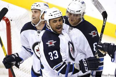 Winnipeg Jets Andrew Ladd, Dustin Byfuglien and  Nik Antropov celebrate their fifth goal against the Columbus Blue Jackets during third period pre-season NHL action in Winnipeg on Tuesday.