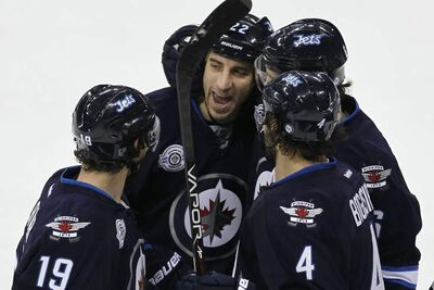 Chris Thorburn (middle) had a throng of well-wishers including Zach Bogosian (4), Ron Hainsey (6) and Jim Slater (19) Tuesday night after his second goal in five games.