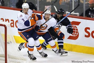 New York Islanders defenceman Andrew MacDonald (47) gets jammed between defenceman Travis Hamonic and Winnipeg Jets defenceman Johnny Oduya (29) during first-period action at the MTS Centre Tuesday.