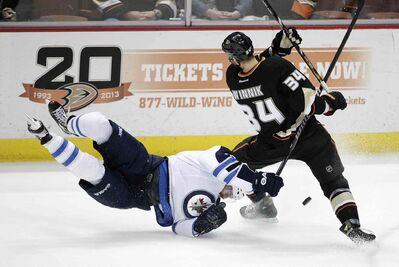 Winnipeg's Andrew Ladd takes a tumble to the ice while fighting for the puck with Anaheim's Daniel Winnik during the first period at the Honda Center Tuesday.