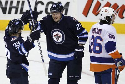Winnipeg Jets players Alexei Ponikarovsky (centre) and Tobias Enstrom (39) celebrate Ponikarovsky's goal against the New York Islanders during first-period NHL action in Winnipeg Sunday.