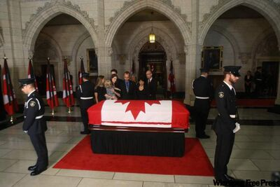 The family of NDP Leader Jack Layton pays their respects as he lies in state on Parliament Hill in Ottawa on Wednesday. Layton died of cancer on Monday.