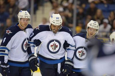 Paul Postma (left) and Toby Enstrom (right) help Dustin Byfuglien back to the bench Friday.