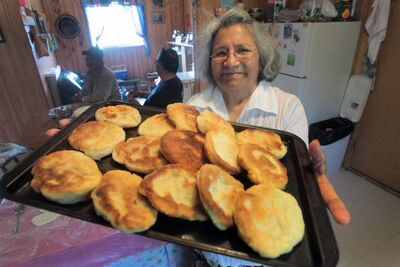 Elder Alice McDougall with fresh bannock she made in a home with no running water. Alice and her spouse Murdo are role models for how to remain healthy while waiting for proper plumbing. They live in a spotless home in Garden Hill without running water, where they stay fit enough to haul water buckets from the lake to supplement what the band delivers.