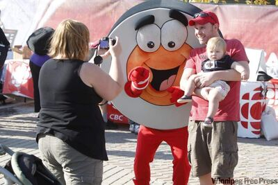 Jennifer Pelland takes a picture of her daughter, McKenna, and her husband, Trevor Didham, with Peter Puck at the NHL Faceoff 2011 at The Forks Thursday.