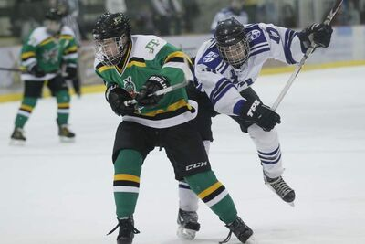 Oak Park Raiders' Dylan Zeke (left) and John Taylor Pipers' Alexander Anderson collide in the Winnipeg High School Hockey League final at the MTS Iceplex Tuesday.