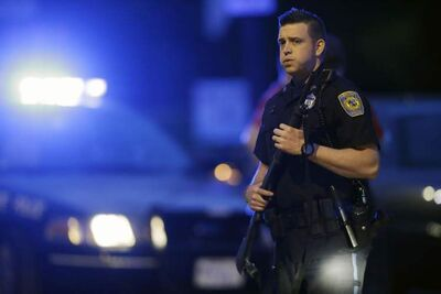 A police officer stands guard at the scene as the search for suspect in the Boston Marathon bombings continues  Friday, April 19, 2013, in Watertown, Mass. Gunfire erupted Friday night amid the manhunt for the surviving suspect in the Boston Marathon bombing, and police in armored vehicles and tactical gear rushed into the Watertown neighborhood in a possible break in the case.