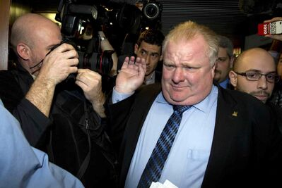 Mayor Rob Ford grabs a photographer's lens as he makes his way through a media scrum at Toronto's city hall Wednesday.